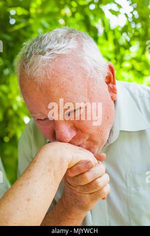 Cerrar senior hombre besando a su esposa la mano en el parque al aire libre en verano