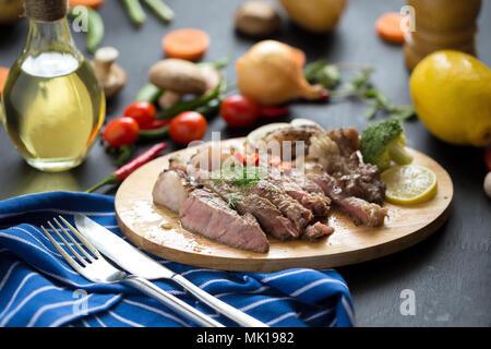 Carne roja a la parrilla con limón y zanahoria en rodajas sobre placa de madera.