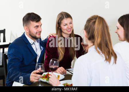 Los amigos están cenando en el restaurante interior. Foto de stock