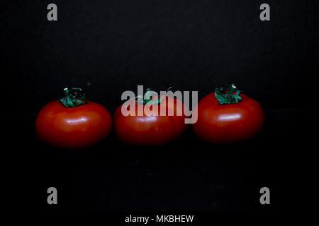 Tomates frescos sobre fondo negro. Conceptos alimentarios. Ilustrativo