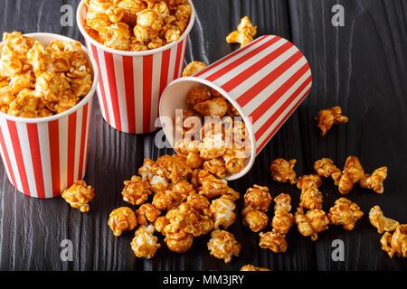Deliciosas palomitas de maíz con caramelo en la cuchara de papel sobre la mesa de madera horizontal contra un fondo oscuro.