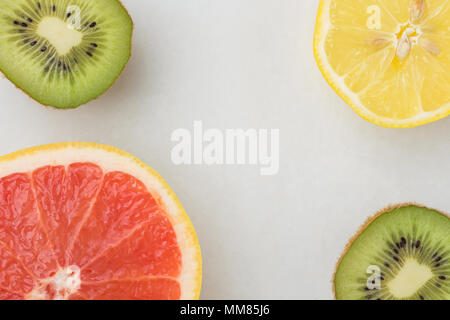 Rebanadas de Kiwi Limón Pomelo jugoso maduras sobre fondo de piedra de mármol blanco. Vida sana vitaminas comer limpio concepto. Trama plana copia laicos Spac Foto de stock