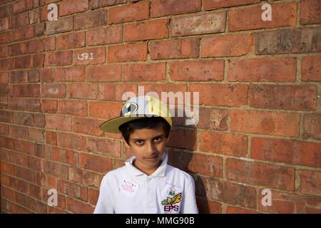 Niño pakistaní en Batman Baseball Hat en pie pared de ladrillo, Rugby, Inglaterra