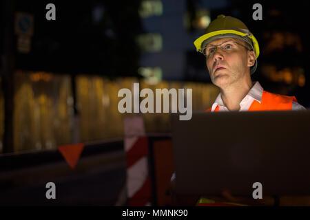 Hombre maduro, trabajador de la construcción en el sitio de construcción en el c