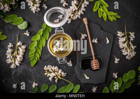 Vista superior de la Miel en tarros de vidrio y flores de acacia sobre fondo negro