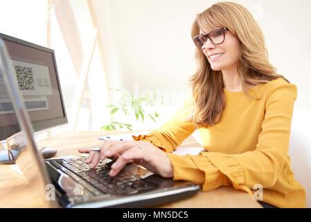 Empresaria madura sonriente escribiendo en el portátil mientras está sentado en la mesa y el trabajo en la oficina.