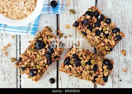 Súper alimento bar de desayuno con avena y arándanos, sobrecarga sobre fondo de madera blanca