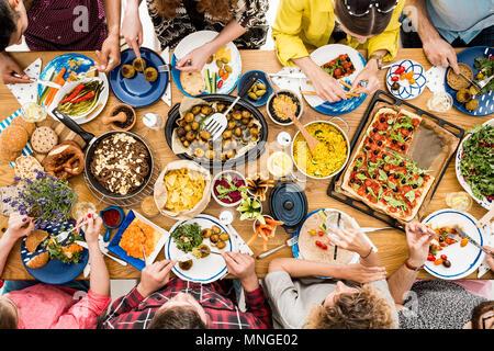 Veggie reunión de amigos a la mesa comunal en restaurante con comida sana raw