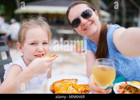 Feliz madre y su adorable hija pequeña en el restaurante al aire libre teniendo selfie mientras tiene un delicioso almuerzo