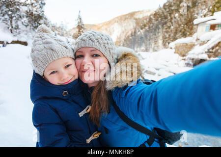 Madre e hija teniendo selfie en el hermoso día de invierno al aire libre