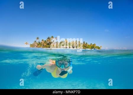 Mujer snorkeling en aguas claras tropicales delante de exótica isla