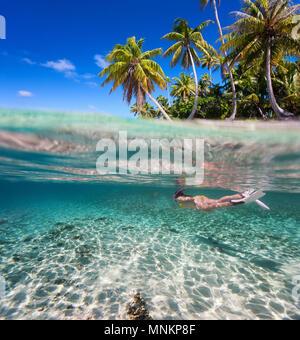 Mujer nadar en aguas claras tropicales delante de exótica isla