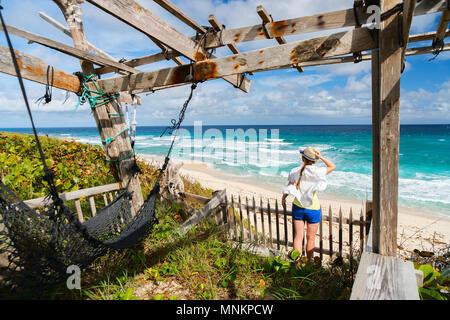Mujer joven disfrutando de la vista de playa tropical en Eleuthera Bahamas Foto de stock
