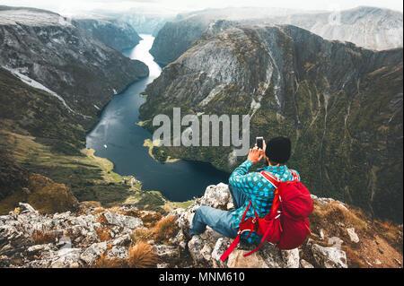 Hombre mochilero smartphone utilizando relajantes en cima de la montaña que viajan solos en Noruega aventura vacaciones activas en el estilo de vida moderna tecnología millennials