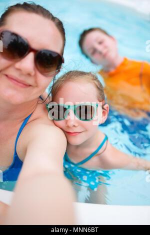 Feliz madre y sus hijos en una piscina al aire libre teniendo selfie en vacaciones tropicales Foto de stock