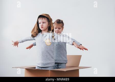 Lúdico de la infancia. Chico divirtiéndose con caja de cartón. Chico fingiendo ser piloto. Chico y chica divirtiéndose en casa