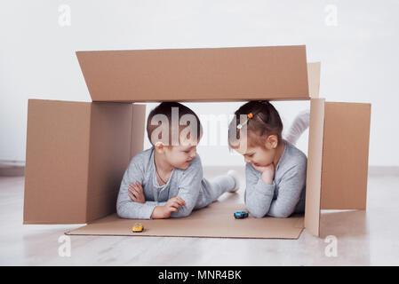 Dos niños pequeños un chico y chica se acaba de mudarse a una nueva casa. Concepto foto .. Los niños se divierten.
