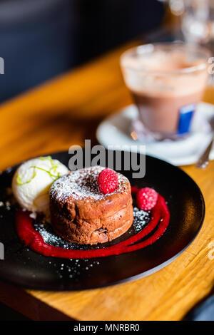 Fondant de chocolate delicioso postre servido con helado de vainilla y bayas frescas Foto de stock