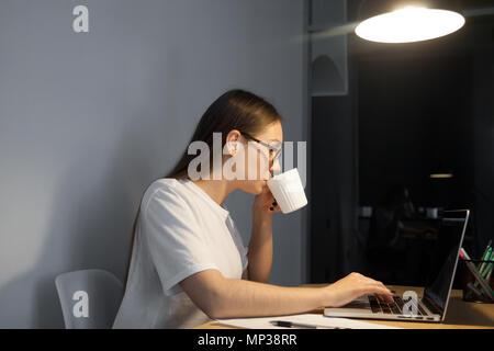 Trabajadora con café mientras trabaja hasta tarde