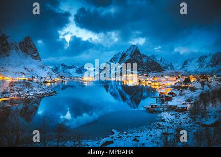 Vista clásica de la famosa aldea de pescadores de Reine con Olstinden pico en el fondo en la mágica noche de invierno crepúsculo, Islas Lofoten, Noruega