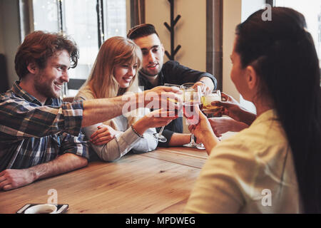 Grupo de jóvenes amigos divirtiéndose y riendo mientras cena en una mesa en el restaurante