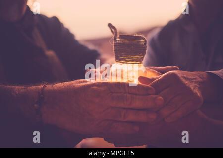 8 manos unidas mantenga un pequeño frasco de vidrio que contiene una luz amarilla.