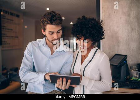 Restaurante dos socios juntos y mirando tableta digital. El hombre y la mujer mediante tableta digital en un café.