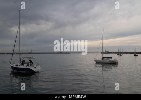 Atardecer en Dun Laoghaire Harbour, barcos de vela, colores suaves, la calma superficial del mar Foto de stock