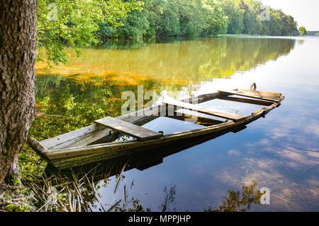 Masurian lago y un arranque de pesca. Coloridas hojas, agua azul y el cielo soleado con algunas nubes blancas. Masuria, región, Polonia.