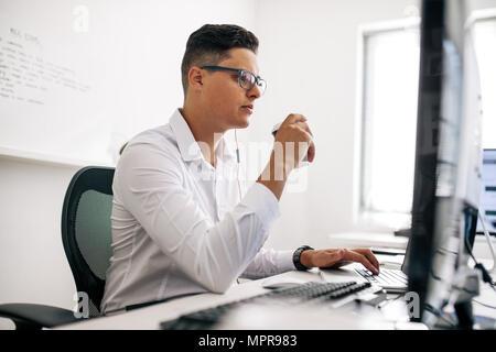Desarrollador de software sonriente sentado en su escritorio de oficina trabajando en el portátil usando auriculares. Llevar gafas hombre trabajando en un PC en la oficina