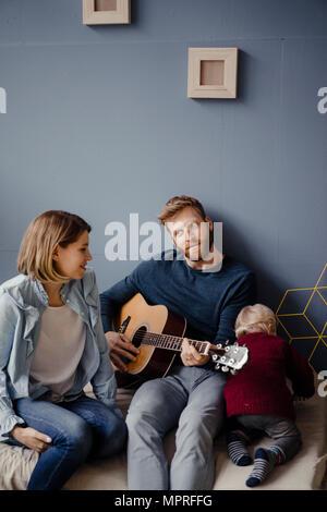 Familia feliz jugando música con su hijo en casa