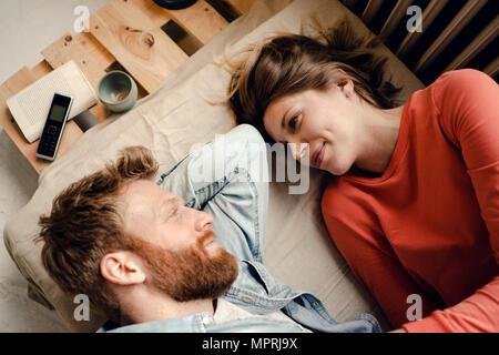 Pareja feliz en casa hablando y escuchando a cada uno de los otros