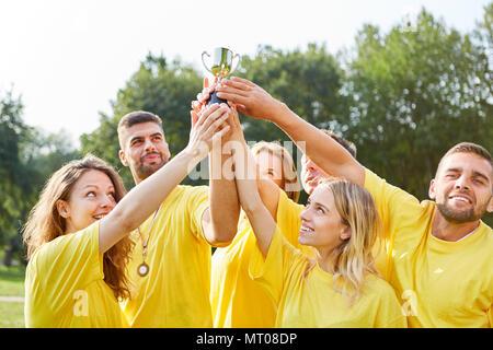 Equipo ganador joven de éxito sostiene con orgullo el trofeo alto en el evento de teambuilding