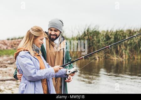 Hermoso par la pesca juntos en día nublado