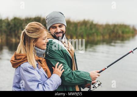 Feliz pareja joven abrazando mientras pescan juntos