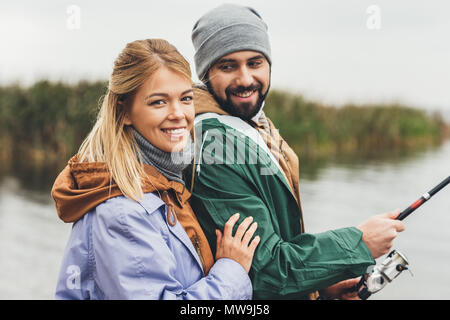 Feliz pareja joven pesca juntos y mirando a la cámara