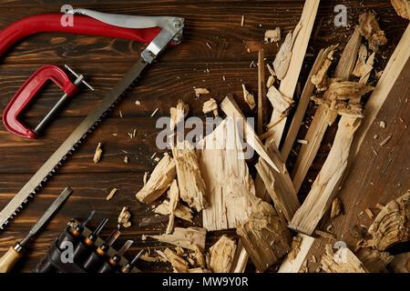 Vista superior de cinceles y sierra caladora con pedazos de madera en la mesa