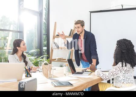 Compañeros de negocios multiethinc tener conversación durante la conferencia en la oficina