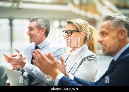 Grupo maduro de empresarios sentados juntos en una mesa en una moderna oficina sonriendo y aplaudiendo después de una presentación