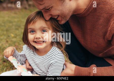 Sonriente chica sentada con su padre en el exterior sosteniendo un bastón de caramelo de azúcar. Padre e hija, pasar tiempo juntos comer azúcar cande.