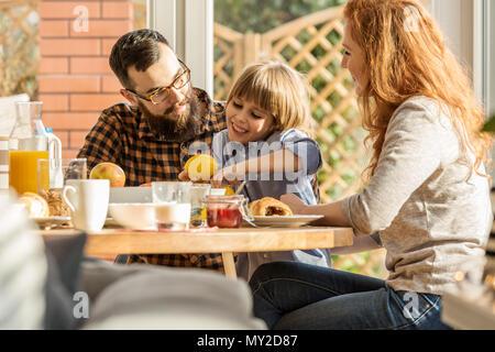Feliz niño sosteniendo un cítrico, sentado entre la madre y el padre. Encantadora familia desayunando