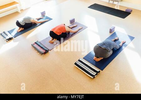 Tres mujeres practicando la postura del niño (balasana) en yoga studio