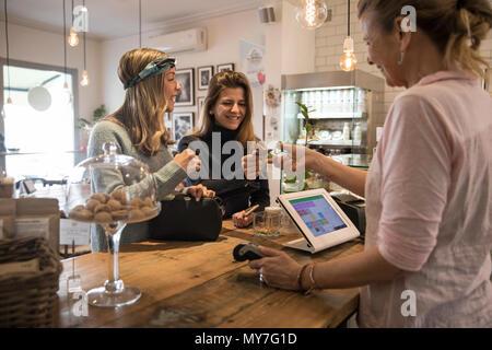 Dos amigas, de pie en el mostrador de la cafetería, entregar la tarjeta de crédito a una tienda de pago