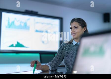 Retrato de mujer de negocios con ordenador portátil y pantallas interactivas con gráficos y diagramas en reunión de negocios