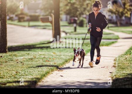 De joven, paseando a un perro a lo largo de vía