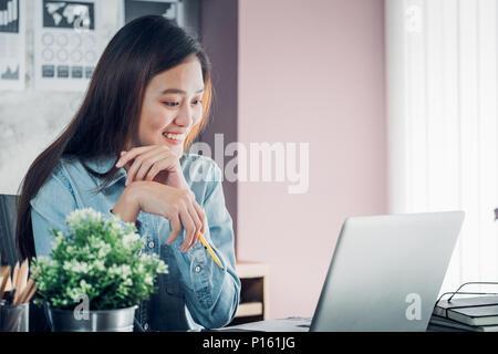 La empresaria asiática pensando con lápiz y mirando hacia abajo en la pantalla de la computadora portátil para planificar el trabajo con la sonrisa en la cara,Office office lifestyle conce Foto de stock
