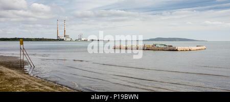 El hormigón en desuso y abandonados en la ZPE de Sandymount Stand Lido Beach en la Bahía de Dublín, con el emblemático chimeneas de Poolbeg Twin Power Station en la distan Foto de stock