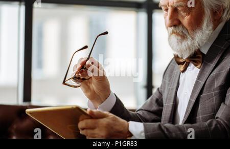 Hombre viejo con malos ojos intentando descry una imagen en la pantalla de la tableta