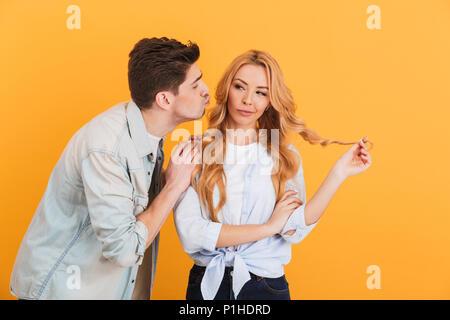 Retrato de mujer encantadora mirando a un lado y vacilar al hombre intentando besar su mejilla aislado sobre fondo amarillo Foto de stock