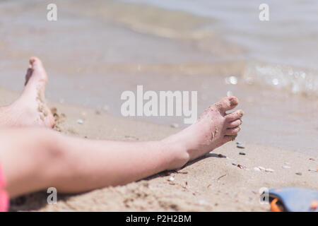 Chico vistiendo el traje de baño rojo descansando sus pies en la arena de la playa en frente del agua